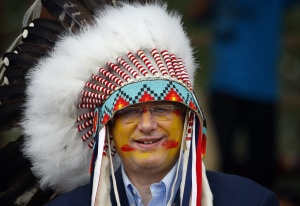 Prime Minister Stephen Harper wears a headdress after being made an honourary chief of the Blood tribe during a ceremony in Stand Off, Alta., Monday, July 11, 2011.THE CANADIAN PRESS/Jeff McIntosh