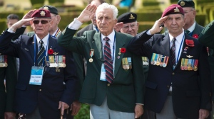 Canadian Korean War veteran's Ellroy Faulkner (left), Joseph Ritchie and Aime Michaud salute as they take part in a Canadian ceremony at the United Nations